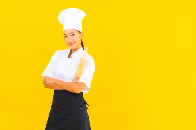 黄色の孤立した背景に麺棒で美しい若いアジアの女性シェフの肖像画