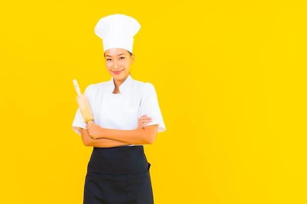 Ritratto di bella giovane donna asiatica chef con mattarello su sfondo giallo isolato