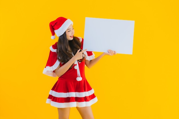 Portrait beautiful young asian woman christmas clothes and hat smile with empty board