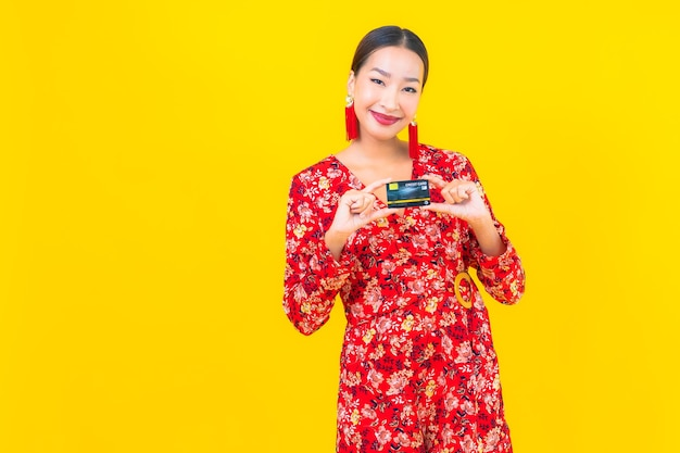 Portrait beautiful young asian woman credit card for shopping on yellow isolated wall