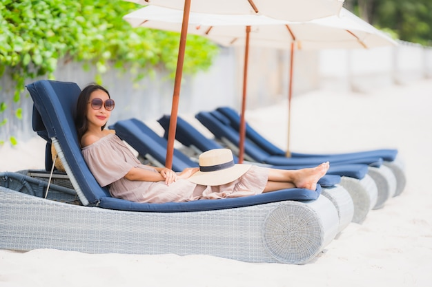 Portrait beautiful young asian woman on the deck chair with umbrella around beach sea ocean