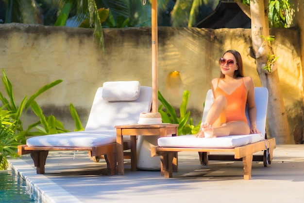 肖像画の美しい若いアジアの女性は、レジャー休暇のためにプールの周りでリラックスをお楽しみください