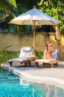 세로 아름 다운 젊은 아시아 여자는 레저 휴가를 위해 수영장 주변에서 휴식을 즐길 수