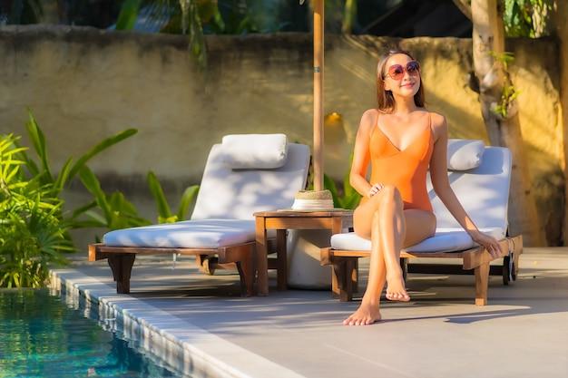 La bella giovane donna asiatica del ritratto gode del relax intorno alla piscina per le vacanze di svago