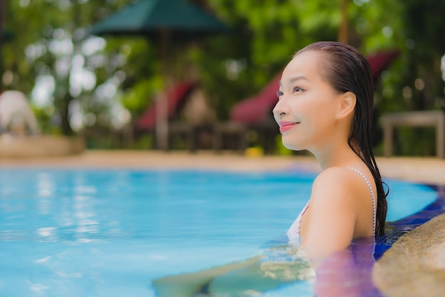 Portrait beautiful young asian woman enjoy relax smile leisure around outdoor swimming pool in hotel