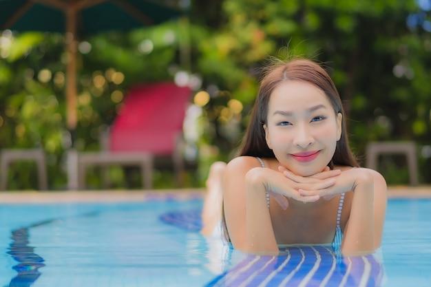 美しい若いアジア女性の肖像画を楽しむホテルの屋外スイミングプールの周りリラックス笑顔笑顔レジャー
