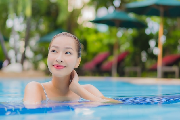 Женщина портрета красивая молодая азиатская наслаждается расслабленным отдыхом улыбки вокруг открытого бассейна в гостинице