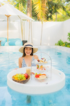 Portrait beautiful young asian woman enjoy with afternoon tea or breakfast floating on swimming pool