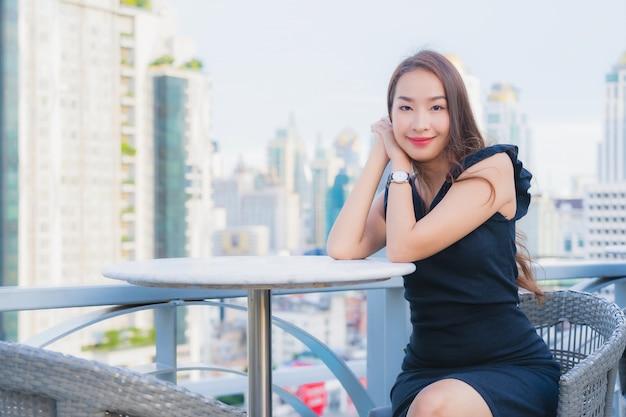 肖像画の美しい若いアジアの女性はカクテルを飲むガラスで楽しんでいます