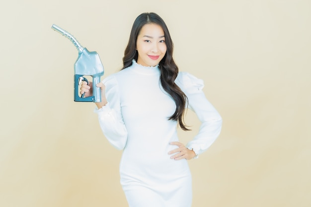 Portrait of beautiful young asian woman feul gas pump on color wall