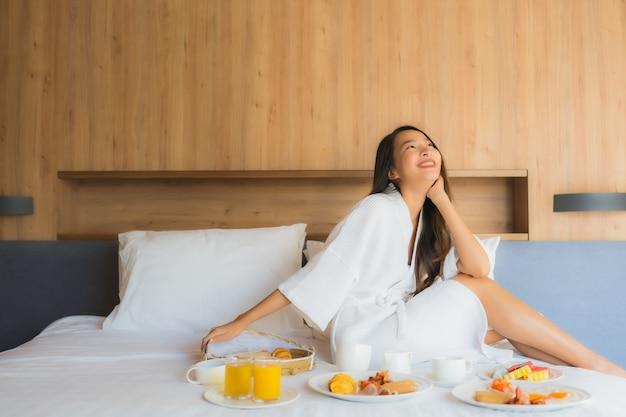 행복 한 초상화 아름 다운 젊은 아시아 여자 침실에서 침대에서 아침 식사를 즐길 수