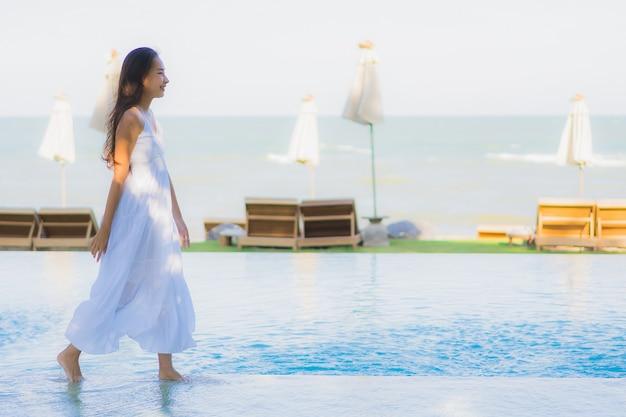 Улыбка красивой молодой азиатской женщины портрета счастливая и ослабляет вокруг бассейна в курорте гостиницы