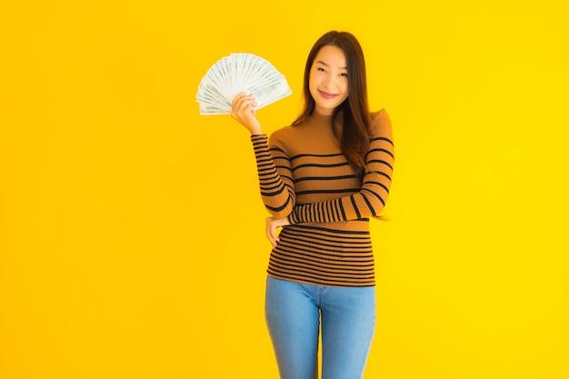 肖像画の美しい若いアジア女性の幸せな笑顔と彼女の手にたくさんの現金が豊富