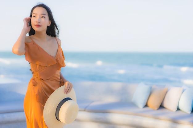 海オーシャンビーチの周りの肖像画美しい若いアジア女性の幸せな笑顔