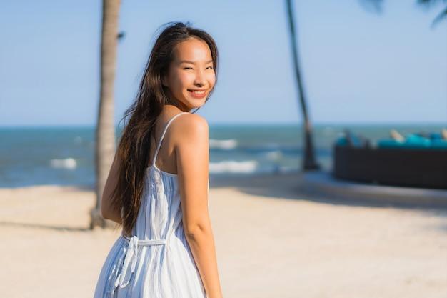 肖像画美しい若いアジア女性の幸せな笑顔がニアリービーチと海の周りリラックス
