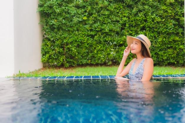 초상화 아름 다운 젊은 아시아 여자 행복 한 미소 호텔 리조트 야외 수영장 주위 휴식