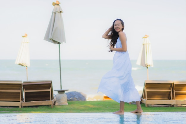 Portrait beautiful young asian woman happy smile and relax around swimming pool in hotel resort