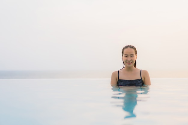 Portrait beautiful young asian woman happy smile relax around swimming pool in hotel resort
