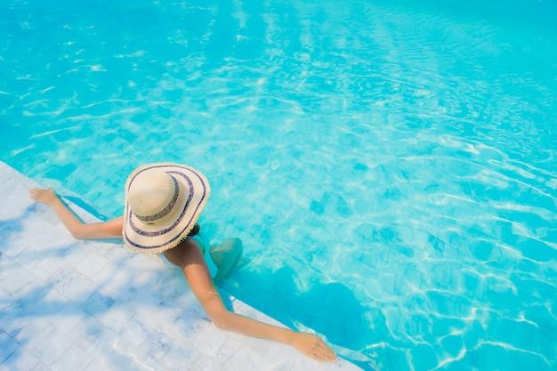 Улыбка красивой молодой азиатской женщины портрета счастливая ослабляет в бассейне на каникулы перемещения