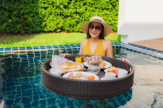 Portrait beautiful young asian woman happy smile relax with breakfast floating around swimming pool