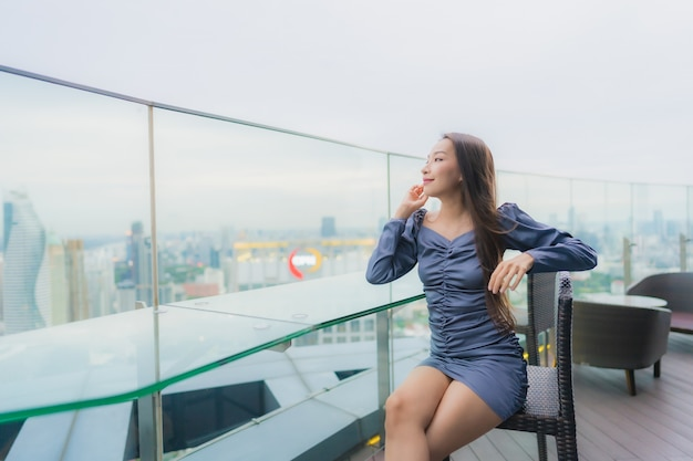 Portrait beautiful young asian woman happy smile on roof top restaurant around city view