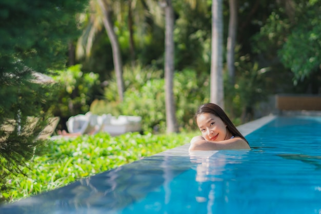Portrait beautiful young asian woman happy smile in swimming pool around resort and hotel