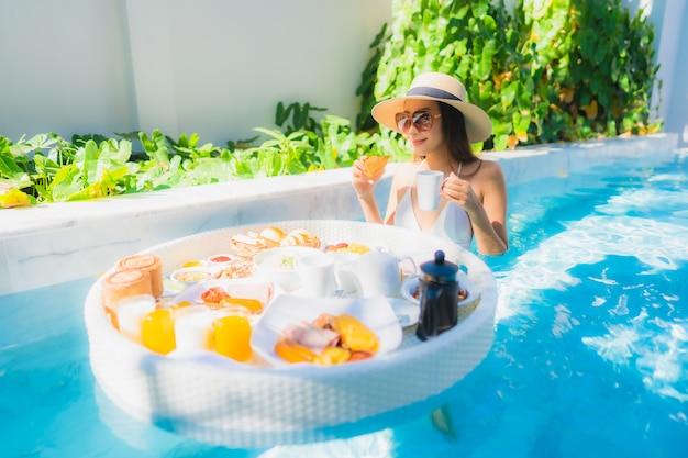 肖像画美しい若いアジア女性の幸せな笑顔のプールでトレイに浮かぶ朝食