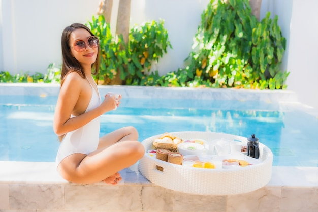 Portrait beautiful young asian woman happy smile with floating breakfast in tray on swimming pool