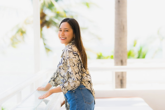 Portrait beautiful young asian woman happy and smile with travel in hotel resort neary sea and beach