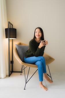 肖像画の美しい若いアジア女性はコーヒーカップを保持し、ソファの椅子に座って