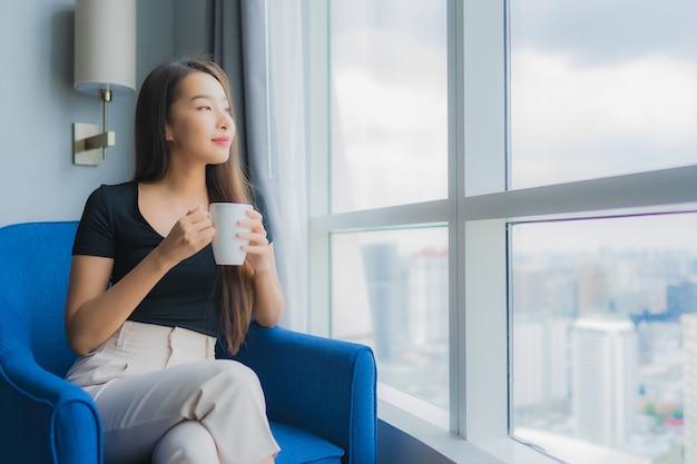 肖像画の美しい若いアジアの女性は、リビングルームのソファーの椅子にコーヒーカップを保持します。