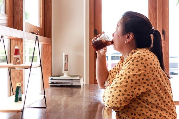 肖像画美しい若いアジアの女性がコーヒーショップでアイスコーヒーカップを保持します。