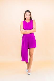 Женщина портрета красивая молодая азиатская в действии на фоне изолированной цветом