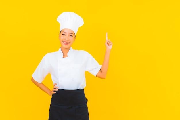 黄色の孤立した背景に帽子とシェフまたは料理の制服を着た美しい若いアジアの女性の肖像画