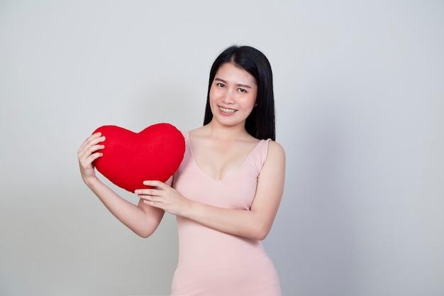 Портрет красивой молодой азиатской женщины в платье показывает подушку в форме сердца, изолированную на светло-сером фоне с копией пространства