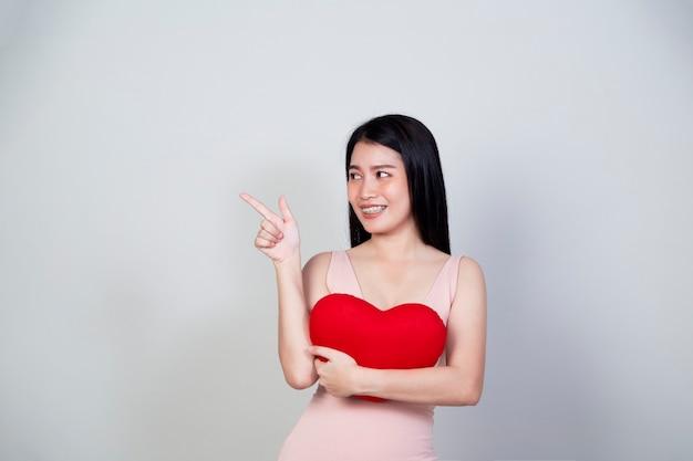 ドレスの肖像画美しい若いアジアの女性は、コピースペースと明るい灰色の背景に分離されたハート形の枕を表示します。