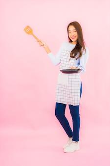 Женщина портрета красивая молодая азиатская в носке кухни с фартуком на розовой изолированной стене