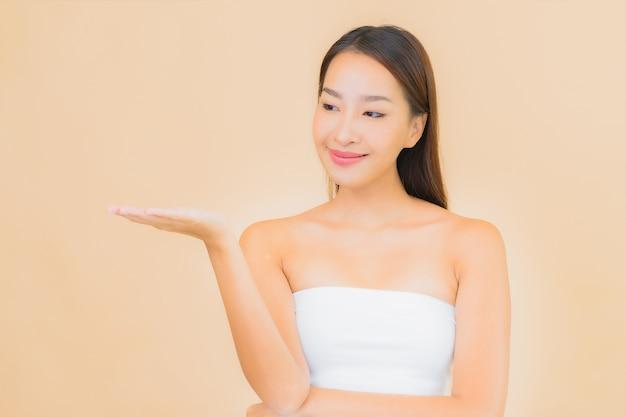 베이지 색에 자연스러운 화장과 스파에서 초상화 아름 다운 젊은 아시아 여자