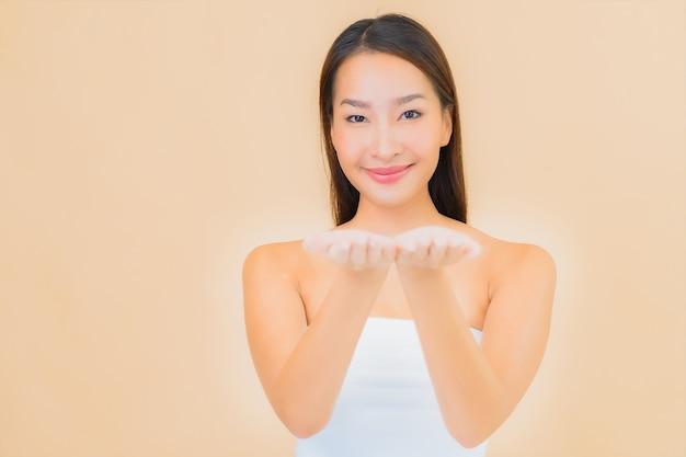 ベージュのナチュラルメイクとスパで美しい若いアジアの女性の肖像画