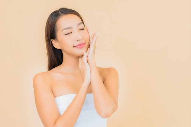 Женщина портрета красивая молодая азиатская в спа с естественным макияжем на бежевом