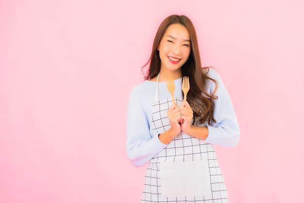 Bella giovane donna asiatica del ritratto nell'usura della cucina con il grembiule sulla parete isolata rosa