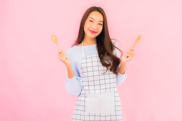 Portrait beautiful young asian woman in kitchen wear with apron on pink isolated wall