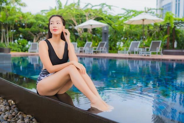 Отдых портрета красивый молодой азиатский ослабляет улыбку вокруг открытого бассейна на каникулы