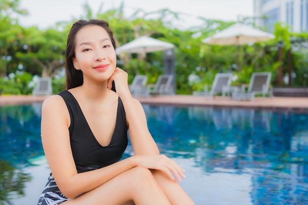 肖像画の美しい若いアジア女性レジャーリラックス休暇の屋外スイミングプールの周りの笑顔