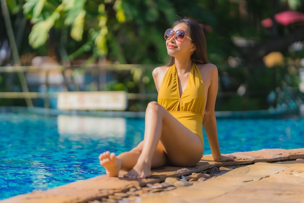 Portrait beautiful young asian woman leisure relax smile and happy around swimming pool in hotel resort