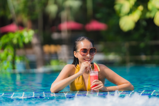 Portrait beautiful young asian woman leisure relax smile with watermelon juice around swimming pool in hotel resort