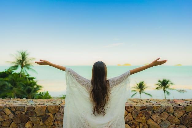 Женщина портрета красивая молодая азиатская смотря океан пляжа моря для ослабляет в путешествии каникул праздника