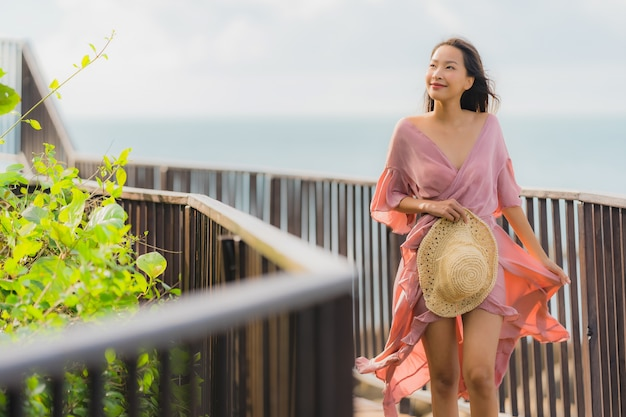 Portrait beautiful young asian woman looking sea beach ocean for relax in holiday vacation travel