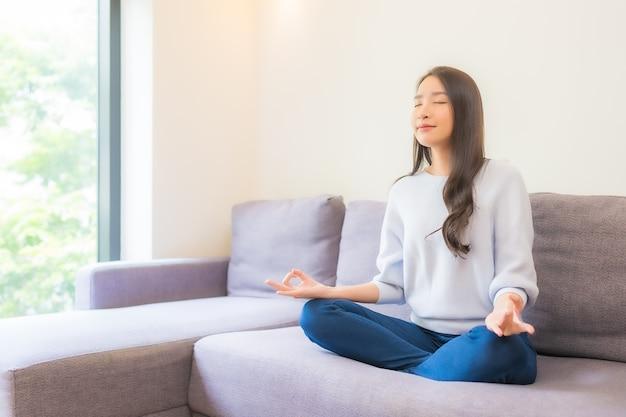 リビングルームのインテリアのソファで美しい若いアジアの女性の瞑想を肖像画