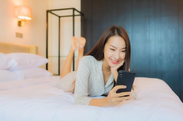 スマート携帯電話が付いているベッドの肖像画美しい若いアジア女性